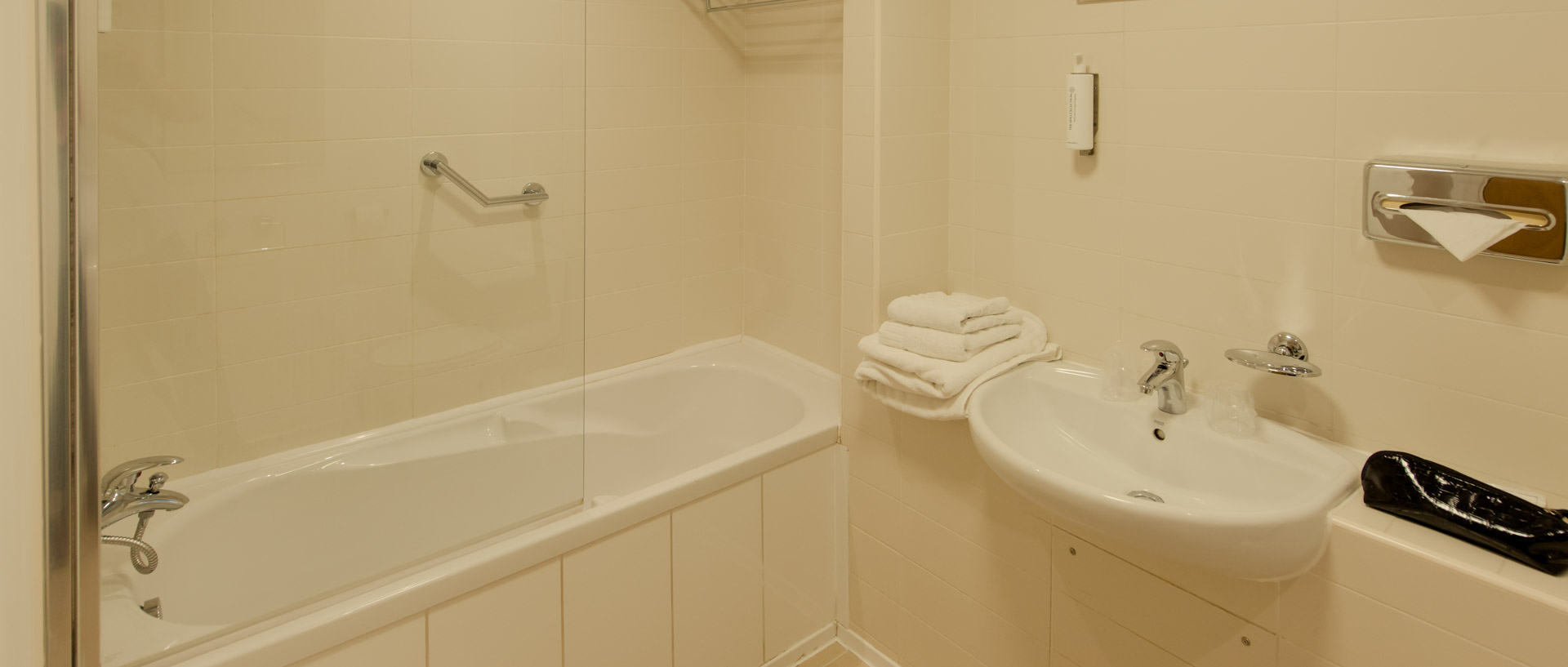 Bright spacious bathroom at PREMIER SUITES Newcastle with shower, bath, sink and toilet
