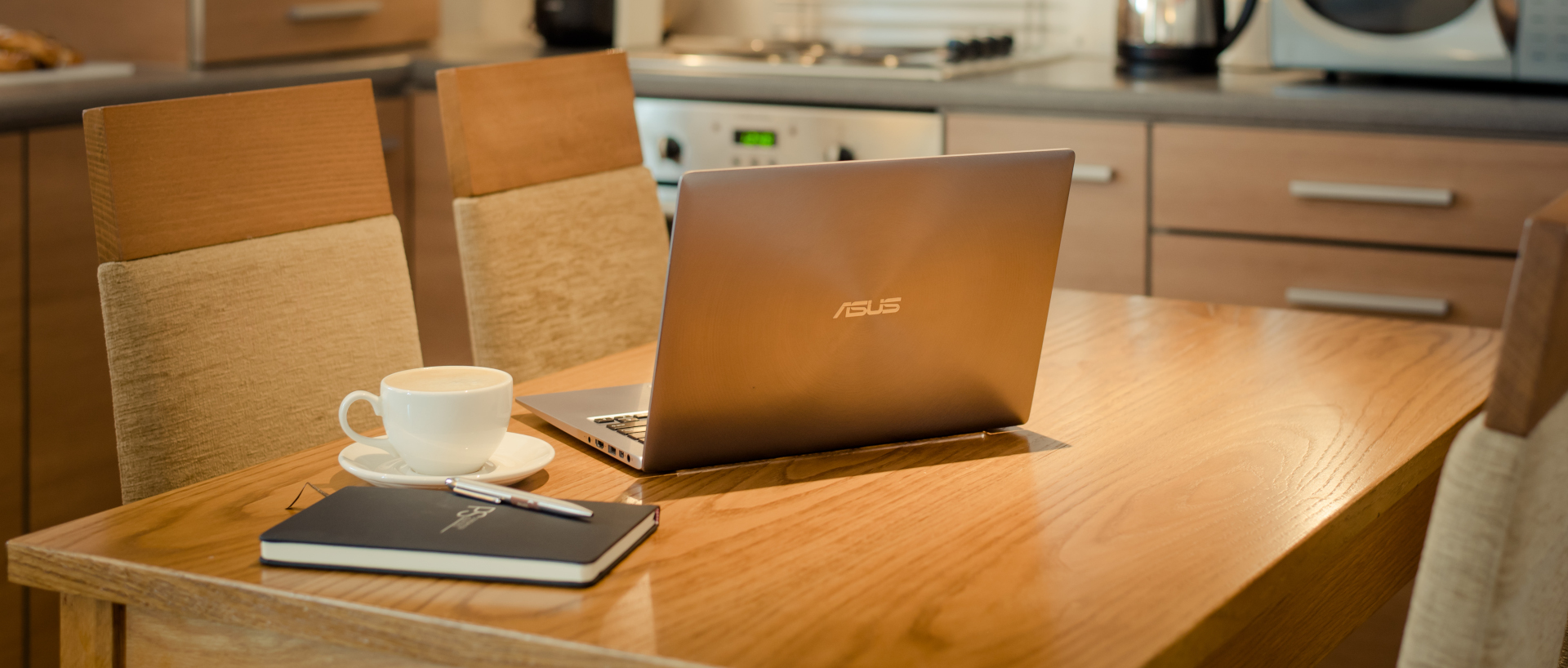 A corporate guests laptop on the kitchen table in PREMIER SUITES Newcastle serviced apartments